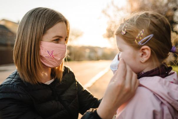Mamma indossa mascherina alla bambina